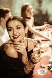 Femme de sourire avec la boisson jouant le tisonnier Photos libres de droits
