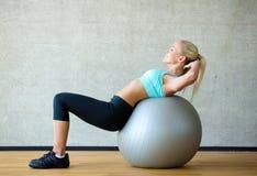 Femme de sourire avec la boule d'exercice dans le gymnase Photographie stock