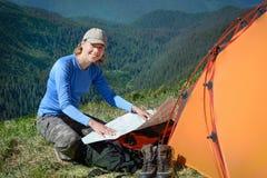 Femme de sourire avec la carte dans les montagnes photographie stock libre de droits
