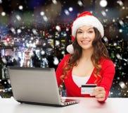 Femme de sourire avec la carte de crédit et l'ordinateur portable Images libres de droits