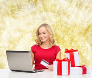 Femme de sourire avec la carte de crédit et l'ordinateur portable Photo stock