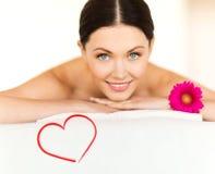 Femme de sourire avec la fleur dans le salon de station thermale Photo libre de droits