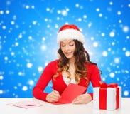 Femme de sourire avec la lettre d'écriture de boîte-cadeau Photos stock