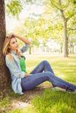Femme de sourire avec la main dans les cheveux tout en se reposant sous l'arbre Image libre de droits