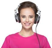 Femme de sourire avec la musique de écoute d'écouteurs Image libre de droits