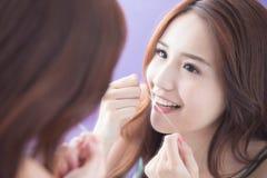 Femme de sourire avec la soie de dents Photo stock
