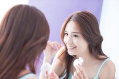 Femme de sourire avec la soie de dents Photos stock