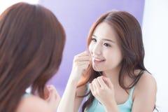 Femme de sourire avec la soie de dents Photographie stock