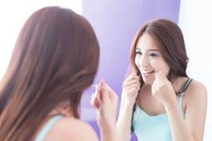 Femme de sourire avec la soie de dents Image stock