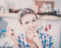 Femme de sourire avec la tasse du café et du journal dans la cuisine Image stock