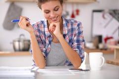 Femme de sourire avec la tasse du café et du journal dedans Images stock