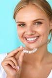 Femme de sourire avec le beau sourire utilisant des dents blanchissant le plateau image libre de droits