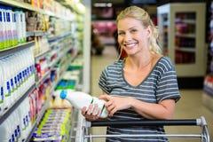 Femme de sourire avec le chariot regardant la bouteille à lait Photographie stock