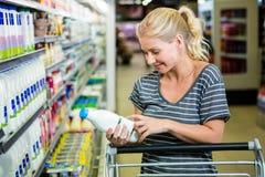 Femme de sourire avec le chariot regardant la bouteille à lait Photographie stock libre de droits