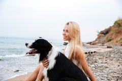 Femme de sourire avec le chien se reposant sur la plage et la pensée Images stock