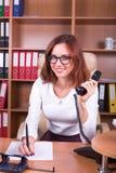 Femme de sourire avec le combiné et stylo dans le bureau Images stock