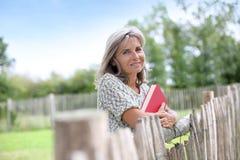 Femme de sourire avec le livre rouge se penchant sur la barrière Photo stock