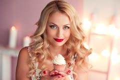 Femme de sourire avec le petit gâteau photographie stock libre de droits