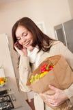Femme de sourire avec le sac à provisions dans la cuisine photo stock