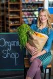 Femme de sourire avec le sac d'épicerie se reposant dans la boutique organique Photo libre de droits