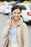 Femme de sourire avec le smartphone au-dessus du taxi dans la ville Photos stock