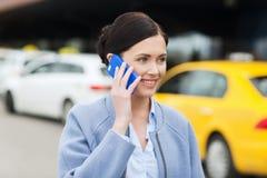 Femme de sourire avec le smartphone au-dessus du taxi dans la ville Photo libre de droits