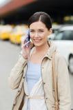Femme de sourire avec le smartphone au-dessus du taxi dans la ville Image libre de droits
