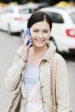 Femme de sourire avec le smartphone au-dessus du taxi dans la ville Images stock