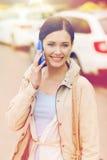 Femme de sourire avec le smartphone au-dessus du taxi dans la ville Images libres de droits