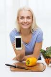Femme de sourire avec le smartphone faisant cuire des légumes Photos libres de droits