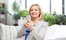 Femme de sourire avec le smartphone textotant ? la maison photo stock