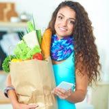 Femme de sourire avec le téléphone portable tenant le panier dans la cuisine Images stock