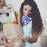 Femme de sourire avec le téléphone portable tenant le panier dans la cuisine Photographie stock libre de droits