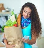 Femme de sourire avec le téléphone portable tenant le panier dans la cuisine Photos libres de droits