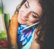 Femme de sourire avec le téléphone portable tenant le panier dans la cuisine image libre de droits