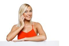 Femme de sourire avec le tableau blanc parlant sur le portable photographie stock libre de droits