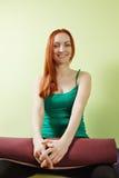 Femme de sourire avec le tapis sur des genoux Photos libres de droits