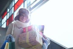 Femme de sourire avec les cadeaux empilés et la fenêtre se tenante prêt de achat pendant l'hiver image stock