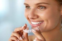 Femme de sourire avec les dents blanches tenant des dents blanchissant le plateau photo libre de droits
