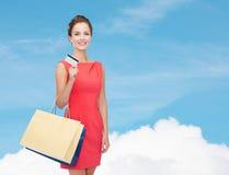 Femme de sourire avec les paniers et la carte en plastique Photographie stock