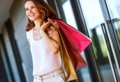 Femme de sourire avec trois paniers examinant la distance photographie stock