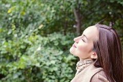 Femme de sourire avec un sourire parfait, marchant le manteau en parc d'automne et en regardant l'appareil-photo Photos libres de droits