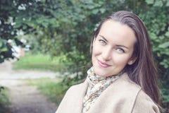 Femme de sourire avec un sourire parfait, marchant le manteau en parc d'automne et en regardant l'appareil-photo Images stock