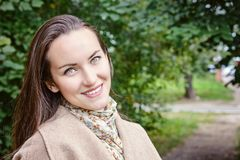 Femme de sourire avec un sourire parfait, marchant le manteau en parc d'automne et en regardant l'appareil-photo Photo stock