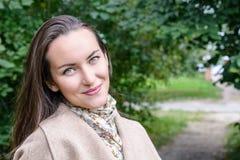 Femme de sourire avec un sourire parfait, marchant le manteau en parc d'automne et en regardant l'appareil-photo Image libre de droits
