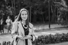 Femme de sourire avec un sourire parfait, marchant le manteau en parc d'automne et en regardant l'appareil-photo Photographie stock libre de droits