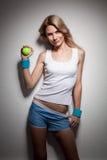 Femme de sourire avec une bille de tennis Images stock