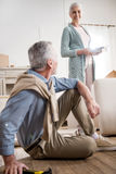 Femme de sourire ayant la discussion avec le mari à la nouvelle maison Photo stock