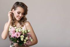 femme de sourire de belle verticale Tenir le bouquet images stock