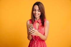 Femme de sourire de brune dans la musique et à l'aide de écoute de robe du smartphone Image stock